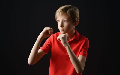 A boy in a red t-shirt with a short haircut on a black background holds his hands like in Boxing, a protective pose
