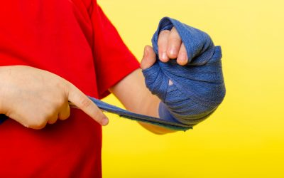 front-view-little-child-boy-tying-his-hand-with-blue-tissue-boxing-red-t-shirt-yellow-wall