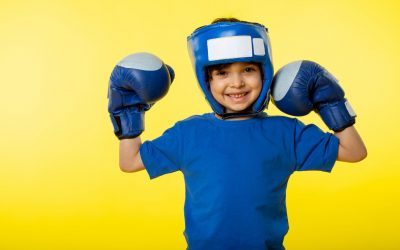 front-view-smiling-cute-boy-blue-boxing-gloves-blue-boxing-helmet-blue-t-shirt-yellow-wall
