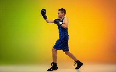 Fighter. Teenage professional boxer training in action, motion isolated on gradient background in neon light. Kicking, boxing. Concept of sport, movement, energy and dynamic, healthy lifestyle.